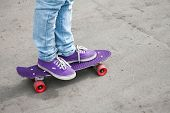 image of snickers  - Riding skateboarder feet in a blue jeans and gumshoes - JPG