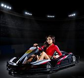 stock photo of karts  - Young girl racer with kart at stadium - JPG