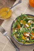 foto of mandarin orange  - Closeup of a plate of arugula salad with mandarins oranges beans sprouts and sliced almonds served with mandarin vinaigrette for healthy lunch - JPG