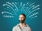 pic of taboo  - Young man with taped mouth and white drawn lines and arrows around his head   - JPG