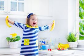 foto of breakfast  - Little girl preparing breakfast in white kitchen. Healthy food for children. Child drinking milk and eating fruit. Happy smiling preschooler kid enjoying morning meal cereal banana and strawberry. ** Note: Shallow depth of field - JPG