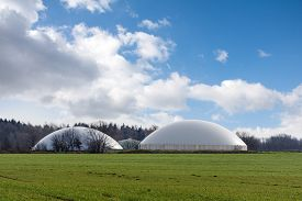 pic of biogas  - biogas plant behind a wide field against blue sky with clouds and copy space - JPG