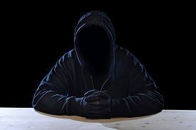 stock photo of hoods  - criminal or terrorist man in gloves black hood and thief mask looking dangerous with hidden identity in secret illegal activity and crime concept with creepy scary terrorist and maniac look - JPG