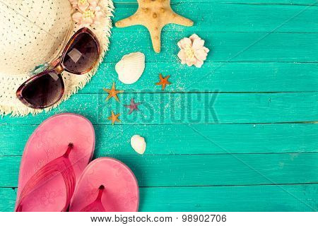 Summer accessories on blue wooden background.