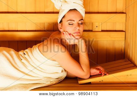 Woman Lying Relaxed In Wooden Sauna