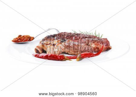 meat food : roast beef steak served on white plate with red pepper , spices , and rosemary isolated over white background