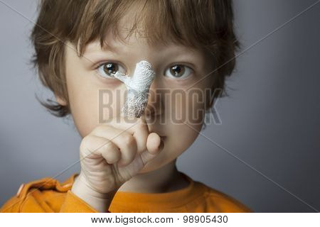 boy with a bandaged wound on his finger (focus on finger)