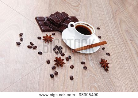sweet hot drink : black coffee in small white cup with beans on a wooden table with stripes of dark chocolate and cinnamon sticks