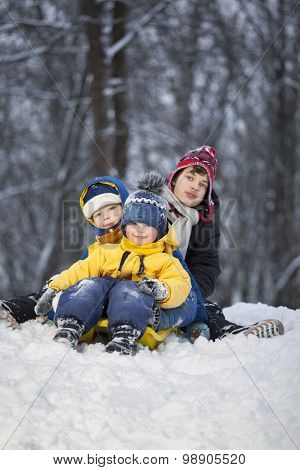 three happy boys on sled play