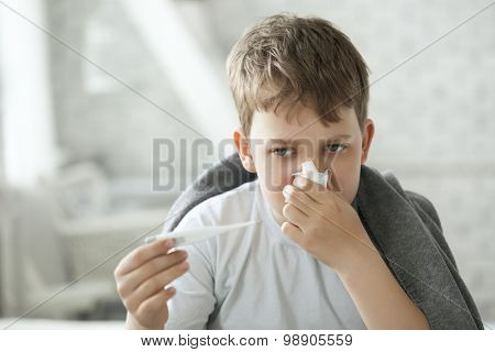 boy wipes his nose with a tissue