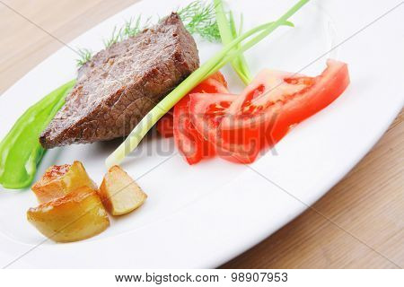 meat savory : grilled beef fillet mignon on white plate with tomatoes apples and pepper over wooden table