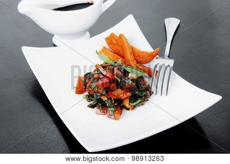 vegetable salad : cherry tomatoes and basil with sweet baked potato served on white plate with sauceboat full black soy sauce on wood