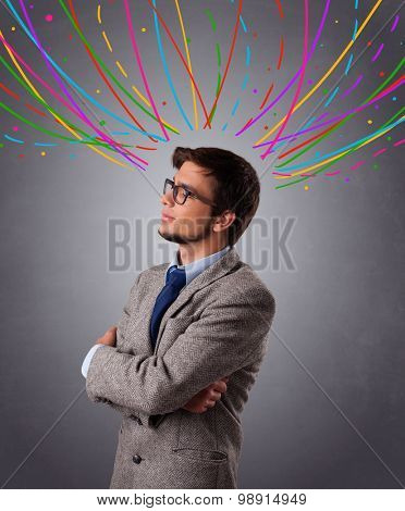 Young man standing and thinking wiht colorful abstract lines overhead
