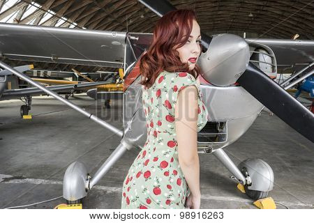 Aircraft, pinup dressed in era of the Second World War, beauty redheaded woman