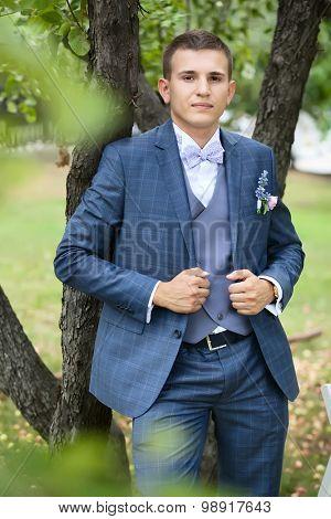 handsome groom in the gray wedding suit in the garden