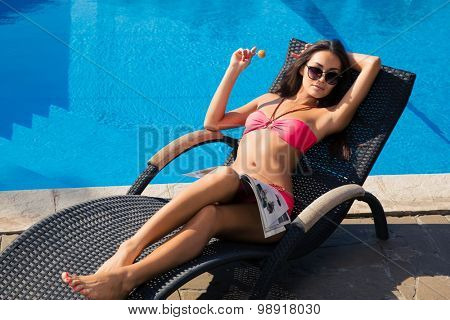 Portrait of a pretty young woman lying on deckchair with lollipop outdoors
