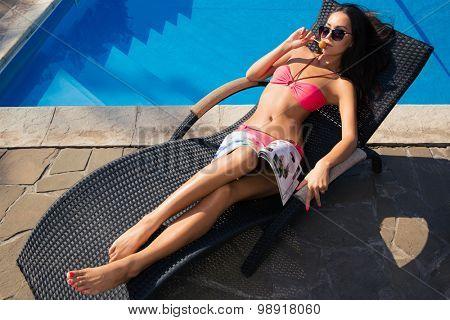 Portrait of a cute woman sunbathing on deckchair with lollipop outdoors