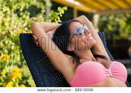 Portrait of happy woman sunbathing on the deckchair outdoors