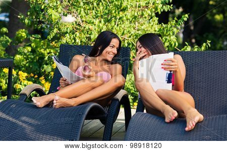 Laughing two young girls reading magazine on the deckchair outdoors