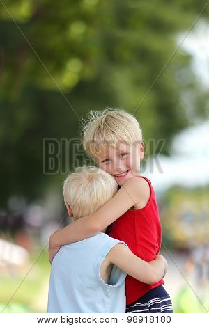 Happy Young Brothers Hug Outside