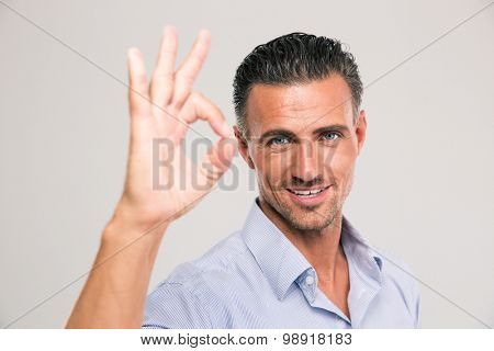 Handsome smiling businessman showing ok sign with fingers over gray background