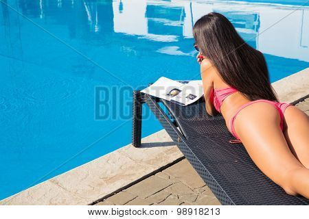 Woman lying on deckchair and reading magazine near swim pool outdoors