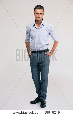 Full length portrait of a handsome businessman standing on gray background and looking at camera