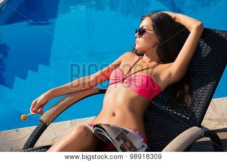 Portrait of a charming girl lying on deckchair with lollipop outdoors