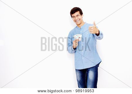 Young hispanic man wearing jeans and glasses holding four aces (spades, hearts, clubs and diamonds) in his hand and showing thumb up hand gesture with smile against white wall - gambling concept