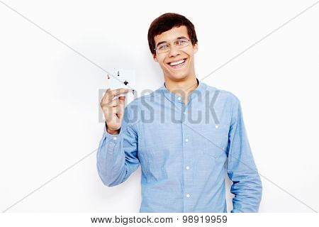 Young hispanic man wearing jeans shirt and glasses smiling and holding two aces (hearts and clubs) in his hand against white wall - gambling concept