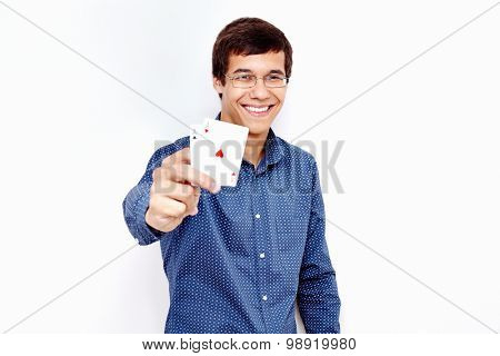 Young hispanic man wearing blue shirt and glasses smiling and holding two aces (clubs and hearts) in his hand against white wall - gambling concept