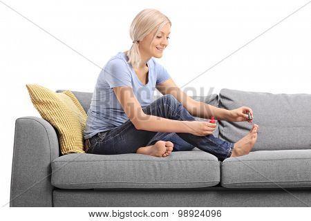 Young blond woman polishing her toenails with a red nail polish seated on a gray sofa isolated on white background