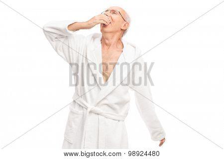 Sleepy senior man in a white bathrobe yawning isolated on white background