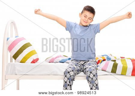 Cute little boy in pajamas stretching himself seated on a bed isolated on white