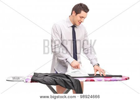 Cheerful young man ironing a pair of pants on an ironing board isolated on white