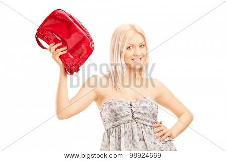 Fashionable blond girl holding a red purse and looking at the camera isolated on white background