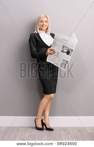 Blond businesswoman holding a newspaper and looking at the camera.The newspaper is custom made, text is Latin and the pictures are my copyright. Additionally property release uploaded.
