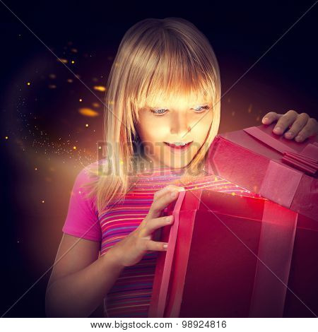 Surprised child with gift box. Happy Little Girl Opening a Present Box. Kid receives a magic gift