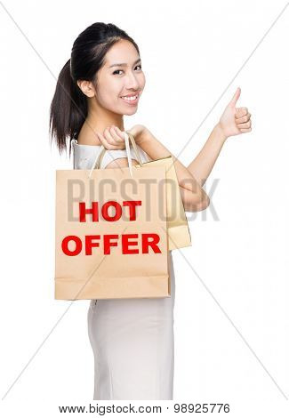 Woman with thumb up gesture and holding shopping bag for showing hot offer