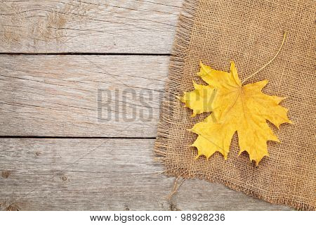 Autumn maple leaves over burlap texture background with copy space