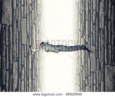 Young troubled businessman trapped between two walls