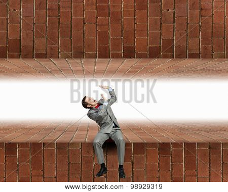 Young scared businessman sitting and looking up