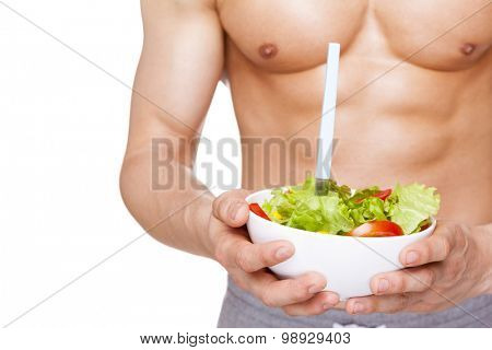 Close-up of a muscular man holding a bowl of salad, isolated on white background