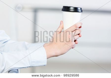 Close up of man's hands standing at balcony with plastic cup