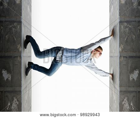 Young man under pressure between two stone walls