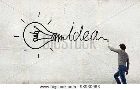 Young businessman standing with back and painting word idea on wall
