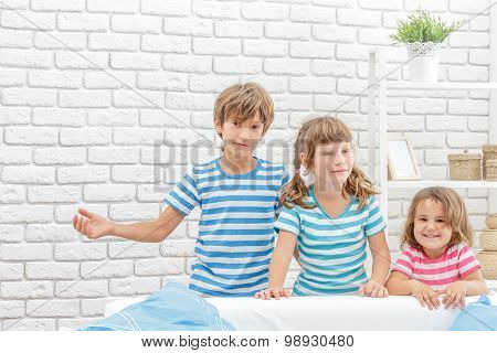 indoor portrait of young happy smiing children, kids, boy and girls, hiding behind sofa at home