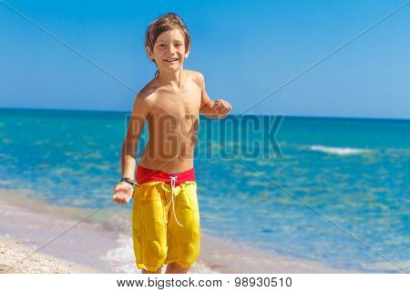 outdoor portrait of young european child boy enjoying summer vacation on beach on natural background
