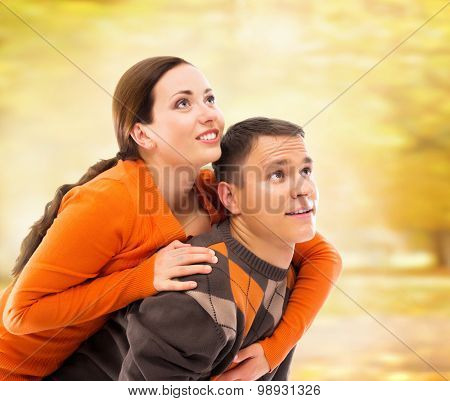 Beautiful and happy couple walking and embracing in the autumn park.