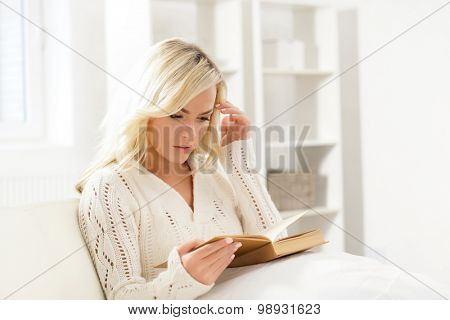 Attractive girl reading a book thoughtfully in the morning.